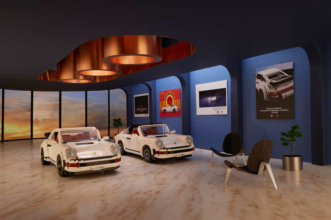 Image of two LEGO Porsche models displayed in a scaled show room